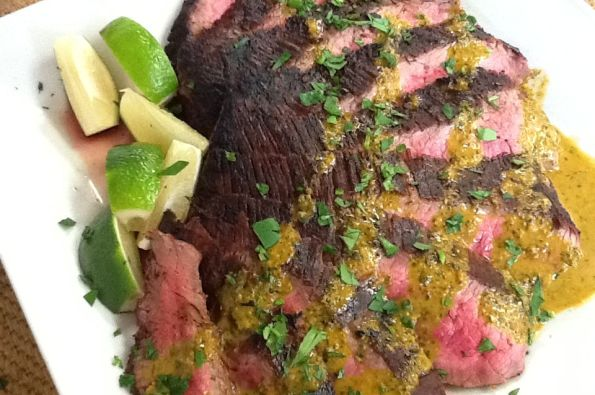 Grilled Chimichurri Flank Steak, with more drizzled on top and some lime wedges on the side.