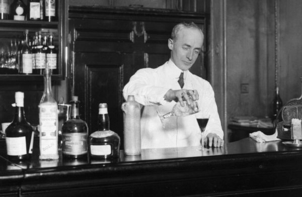"Bartender Harry Craddock makes potable magic at the Savoy Hotel in London in 1926. Craddock popularized the 'Corpse Reviver,' one of the drinks featured in ""Let's Bring Back: Cocktail Edition."" Topical Press Agency/Getty Images"