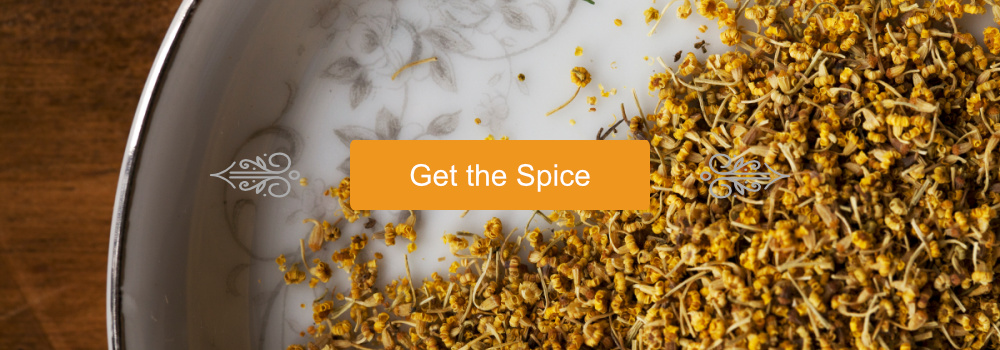 """""""Get the Spice"""" button with scroll embellishments upon a Fennel Pollen background"""